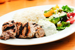 Traditional greek dinner with lamb kabobs, salad, rice and tzatz Stock Images