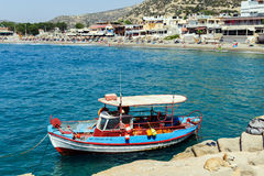 Traditional greek fishing boat stays parked near beach of Matala town on Crete island, Greece Stock Photos