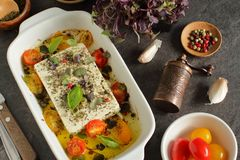 Traditional Greek food with baked feta cheese and summer vegetables. On a rustic table royalty free stock photo