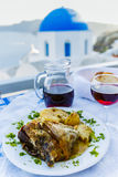 Traditional Greek food and homemade red wine. On table with Oia view royalty free stock images