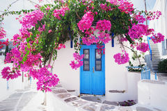 Traditional greek house with flowers in Paros island, Greece. Blue door surrounded by magenta flowers Royalty Free Stock Images