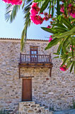 Traditional greek house made of stone in surrounded by flowers at the island of Amoulani Stock Image