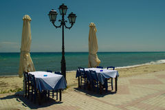 Traditional greek outdoor restaurant. Table and chairs in traditional greek tavern with blue table and chairs overlooking Mediterranean sea. foto taken   28.05 Royalty Free Stock Images