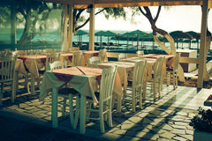 Traditional greek outdoor restaurant on terrace. Overlooking Mediterranean sea (Greece ). empty table at an street sea restaurant. toned image Stock Photography
