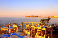 Traditional greek outdoor restaurant on terrace at street villag Stock Photography