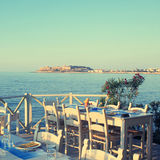 Traditional greek outdoor restaurant on terrace at street villag Royalty Free Stock Photo