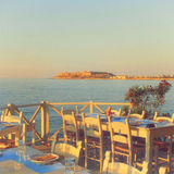 Traditional greek outdoor restaurant on terrace at street villag Royalty Free Stock Photos