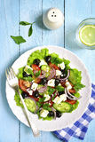 Traditional greek salad on a white plate over rustic wooden back Stock Photography