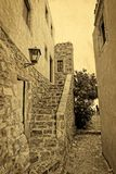 Traditional greek street vintage postcard. Greece monemvasia traditional street in main capitol in mani Peloponnese with sea background stock photos