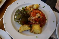 Traditional greek summer dish, baked stuffed vegetables, tomatoes, peppers and roasted potatoes with chopped mint stock photo