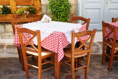 Traditional Greek Tavern Table. Covered in Red and White Gingham Checkered Tablecloth Royalty Free Stock Photo