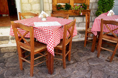 Traditional Greek Tavern Tables. Covered in Red and White Checkered Gingham Tablecloth Stock Photo