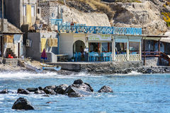 Traditional Greek tavern with tourists at rocky coastline of Santorini island Stock Photos
