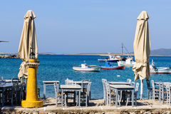 Traditional Greek taverna. On the seafront on the beach - bright chairs and table, Alyki village, Paros island, Cyclades, Greece royalty free stock image