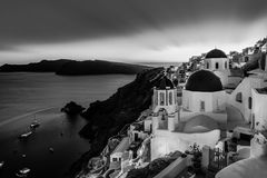 Traditional greek village of Oia in black and white, Santorini island, Greece. Black and white cityscape of Oia, traditional greek village with blue domes of Stock Photos