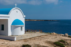 Traditional Greek white chapel with a blue roof on the seaside. Stock Photography