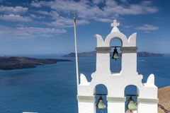 Traditional Greek white church arch with cross and bells in vill. Age Fira of Cyclades Island Santorini Greece Stock Photo
