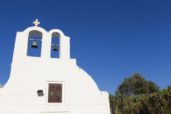 Traditional Greek white church arch with cross and bells in vill Royalty Free Stock Photo