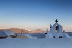 Traditional Greek white church arch with cross and bells in vill. Age Oia of Cyclades Island Santorini Greece Royalty Free Stock Photos