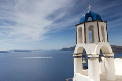 Traditional Greek white church arch with cross and bells in vill Stock Images