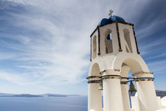 Traditional Greek white church arch with cross and bells in vill Royalty Free Stock Images