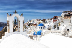 Traditional Greek white church arch with cross and bells in vill. Age Oia of Cyclades Island Santorini Greece Stock Photos