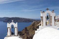 Traditional Greek white church arch with cross and bells in vill. Age Oia of Cyclades Island Santorini Greece Royalty Free Stock Image