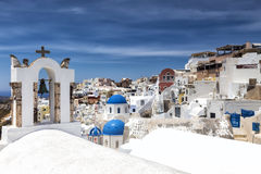 Traditional Greek white church arch with cross and bells in vill Royalty Free Stock Photos