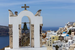 Traditional Greek white church arch with cross and bells in vill. Age Oia of Cyclades Island Santorini Greece Royalty Free Stock Images