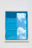 Traditional greek window against a white wall and the cloudy sky Stock Image