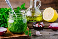 Traditional green chimichurri sauce with fresh parsley, red onion, garlic, olive oil in glass Stock Images