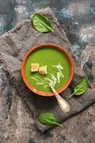 Traditional green cream soup with spinach is served with croutons. Rustic background, top view, flat lay. stock image