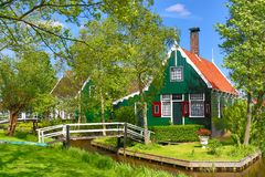 Traditional green dutch house with little wooden bridge against blue sky in the Zaanse Schans village, Netherlands. Famous tourism. Place royalty free stock photos