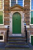 Traditional green front door with steps in Amsterdam Royalty Free Stock Photos
