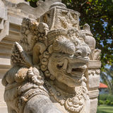 Traditional guard demon statue carved in dark stone in Bali Royalty Free Stock Photos