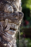 Traditional guard demon statue carved in dark stone Royalty Free Stock Image