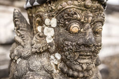 Traditional guard demon statue carved in dark stone Stock Photos