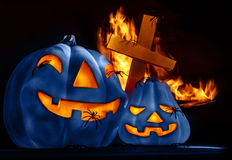 Traditional Halloween decorations. Closeup on scary Halloween decorations, eerie glowing blue carved pumpkin, eldritch spiders, cross and burning fire on Royalty Free Stock Photos