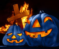 Traditional Halloween decorations. Closeup on scary Halloween decorations, eerie glowing blue carved pumpkin, eldritch spiders, cross and burning fire on Royalty Free Stock Images