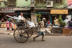 Traditional hand pulled indian rickshaw driver working on the street in Kolkata, West Bengal, India Royalty Free Stock Images