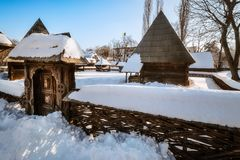 Traditional handcrafted gate and a rural Romanian homestead. Traditional handcrafted gate and a rural homestead covered in snow at the Village Museum in stock images