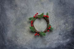Traditional Handmade Christmas Wreath Green Fir Tree Branches Twigs Holly Berries on Grungy Dark Stone Background. Top View Royalty Free Stock Image