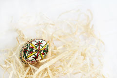 Traditional handmade  Easter egg in straw on white cloth Stock Images