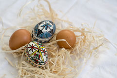 Traditional handmade Easter eggs in straw on white cloth. And few organic fresh eggs in background. Traditional pattern from Bucovina royalty free stock photos