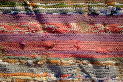 Traditional Handmade old colored carpet with grains of sand Stock Photos