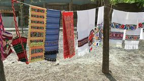 Traditional handmade romanian carpets colorful. Colorful traditional handmade romanian carpets and shoulder bag textile hanging in the wind stock video