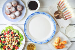 Traditional Hanukkah dishes on the white wooden table top view. Sufganiot , fried cheese , Hanukkah salad with menorah and seasoning on the white wooden table