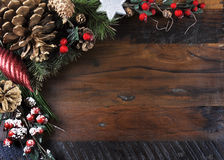 Traditional Happy Holidays and Christmas background. With pine cones and festive ornaments on dark recycled wood with copy space for your text here royalty free stock images