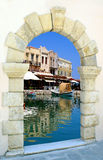 Traditional harbor through an old door in Crete is Stock Photo