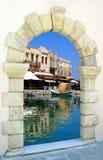 Traditional Harbor Through An Old Door In Crete Is Stock Photo